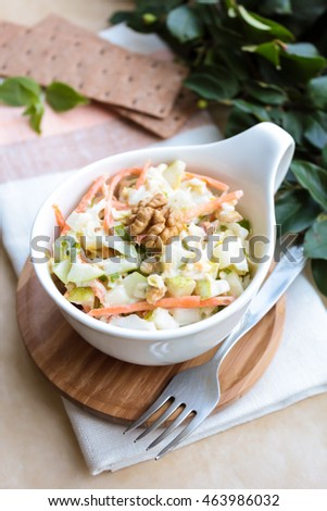 Fresh salad with white cabbage, carrot, apples and pears with walnuts and yogurt dressing in a bowl, selective focus