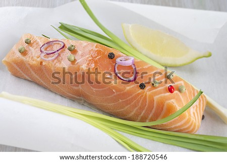 fresh salmon filet with vegetable ready to cook on parchment - stock photo