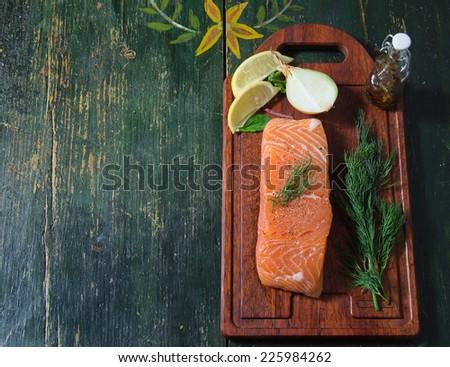 Fresh salmon fillet, lemon, dill, onion. Vintage table background. - stock photo