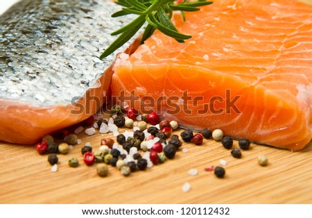Fresh salmon fillet on wooden board with pepper and rosemary - stock photo