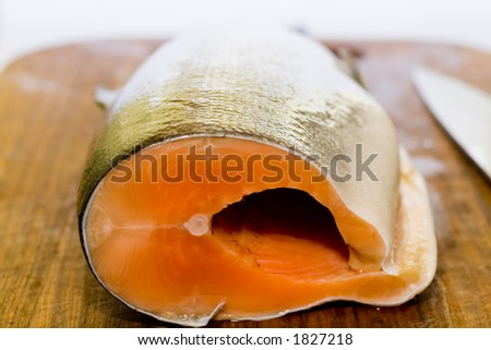 Fresh salmon fish with knife on wooden cooking desk - stock photo