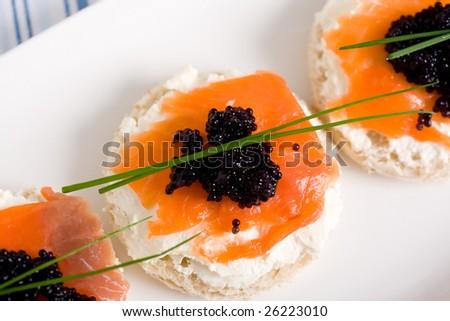 fresh salmon mini sandwich with black caviar - stock photo