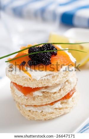 fresh salmon mini sandwich with black caviar. shallow dof - stock photo
