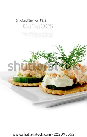 Fresh salmon pate canapes with cream cheese and dill garnish against a white background. Copy space. - stock photo