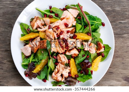 Fresh Salmon Salad with vegetables, pomegranate and orange - stock photo