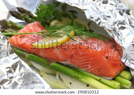 fresh salmon with asparagus in foil paper, ready for cooking - stock photo