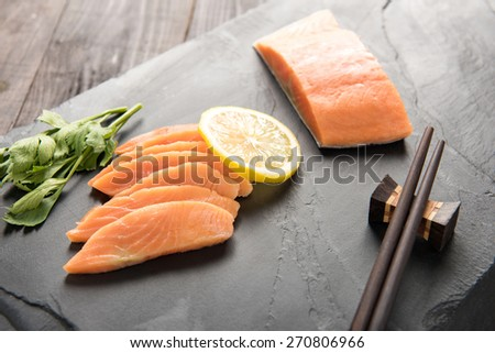 Fresh salmon with lemon on black background - stock photo