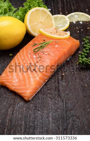 Fresh salmon with lemon on wooden table - stock photo