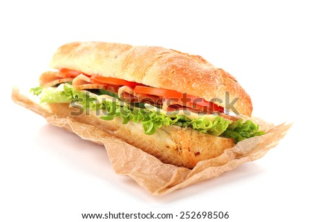 Fresh sandwich on parchment isolated on white - stock photo