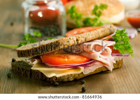 Fresh sandwich with cheese, ham and tomato on wooden table - stock photo