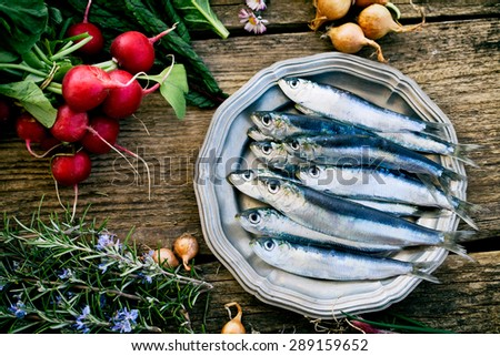 Fresh sardines. Fish with vegetables. Mediterranean fish on plate - stock photo