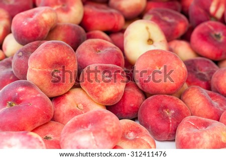 Fresh saturn peaches (or donut peaches) piled up - stock photo