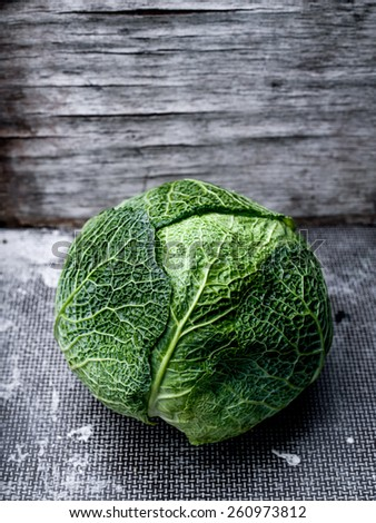 Fresh savoy cabbage on wooden background - stock photo