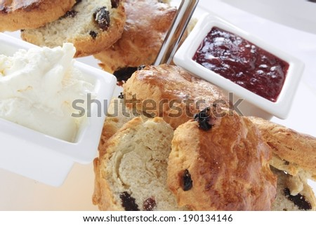 fresh scones with clotted cream and jam - stock photo