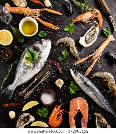 Fresh seafood on black stone, close-up. - stock photo