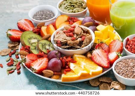 fresh seasonal fruits, juices and superfoods on rustic background, closeup, horizontal - stock photo