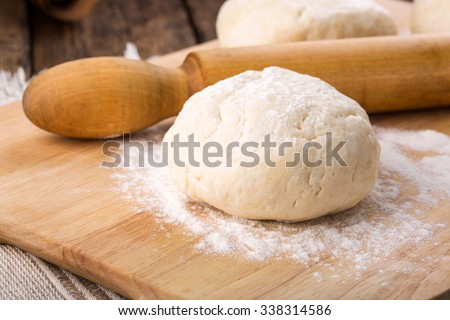 Fresh shortcrust dough pastry and rolling pin on table. Unrolled and unbaked. Ready for baking.