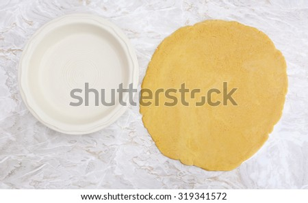 Fresh shortcrust pastry rolled out in a circle, ready to line ceramic pie dish - stock photo