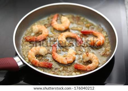 fresh shrimps being fried on a pan - very shallow DOF - stock photo