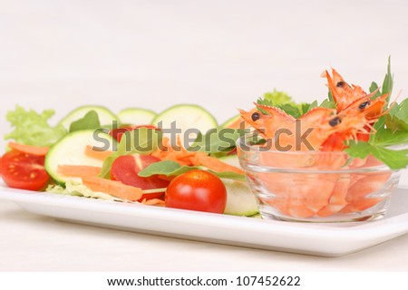Fresh shrimps in a small glass bowl with mixed salad. Selective focus, shallow DOF