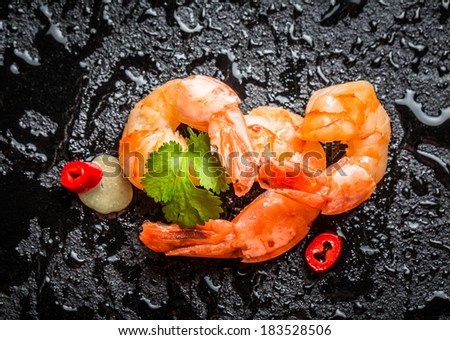 Fresh shrimps on black rock with water drops - stock photo