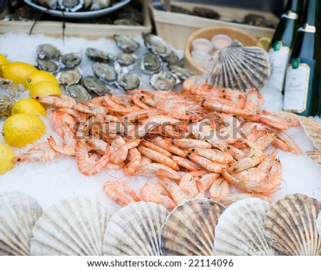 fresh shrimps on ice with lemon and oysters - stock photo