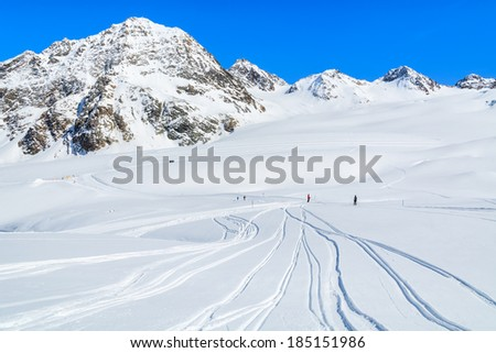 Fresh ski tracks in snow on slopes in Pitztal winter mountain resort, Austrian Alps - stock photo