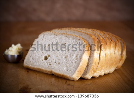 Fresh sliced bread on a wooden table with butter - stock photo
