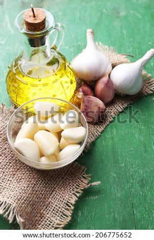 Fresh sliced garlic in glass bowl and oil in glass bottle, on wooden background - stock photo
