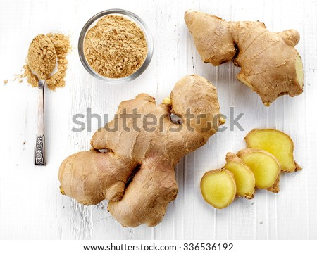 Fresh sliced ginger root and ground ginger on white wooden background; top view - stock photo