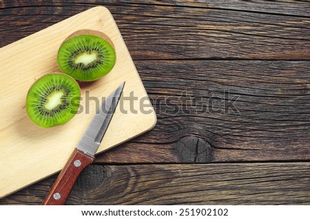 Fresh sliced kiwi fruit and knife on wooden board, top view - stock photo