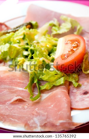 Fresh Sliced raw beef meat with leaf lettuce on table - stock photo