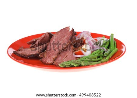 fresh sliced roast beef on red plate with tomatoes and asparagus isolated on white background
