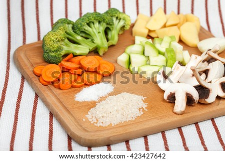 Fresh sliced soup ingredients on wooden cutting board. Top-side view, low aperture shot - stock photo