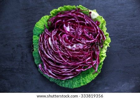Fresh slices of red cabbage in green cabbage leaf on old blue stone background. - stock photo