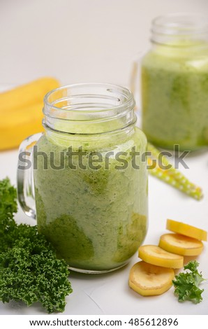 Fresh smoothie with kale and banana on white background, selective focus