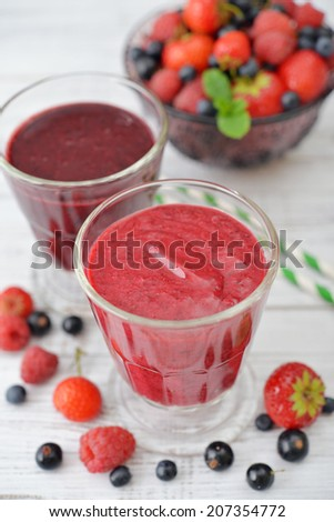 Fresh smoothies with ripe berries in glass vase  on light background - stock photo