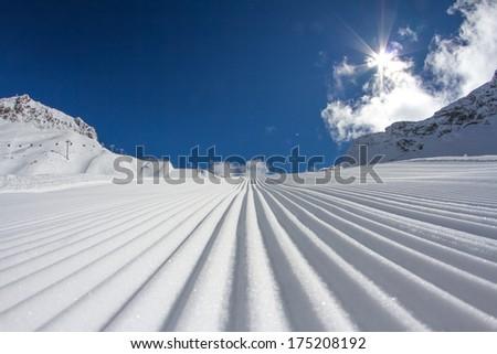 Fresh snow groomer tracks on a ski piste - stock photo