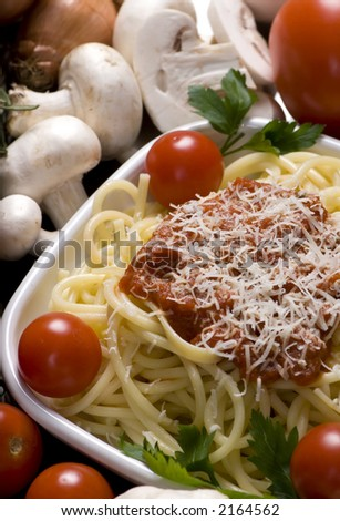 Fresh spaghetti and sauce, surrounded by all the ingredients - stock photo