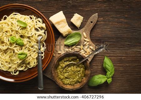 Fresh spaghetti with basil pesto on wooden background - stock photo