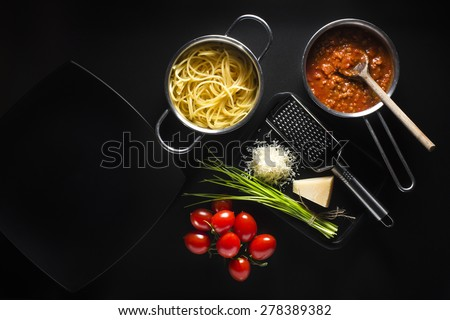 Fresh spaghetti with tomatoes sauce and parmesan on black background