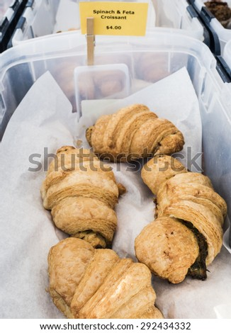Fresh spinach and feta croissants for sale at local farm market. - stock photo