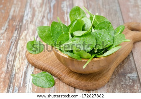 Fresh spinach in a wooden bowl on the table
