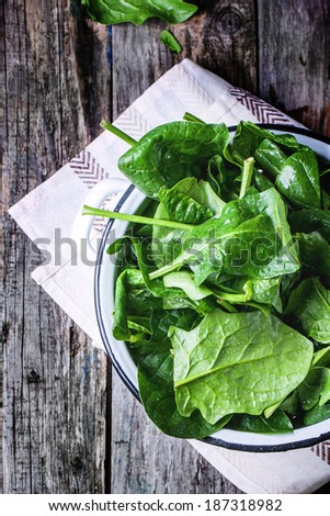 Fresh spinach in metal colander over wooden background. Top view - stock photo