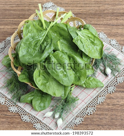 Fresh spinach leaves in a wicker basket - stock photo