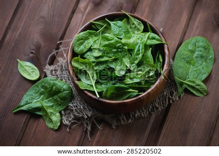 Fresh spinach leaves over dark brown wooden background, selective focus - stock photo