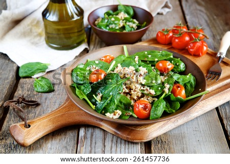 Fresh spinach salad with quinoa and roasted tomatoes - stock photo