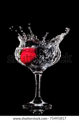 fresh splashing strawberry into a wet cocktail glass