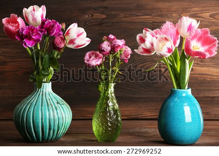 Fresh spring flowers on wooden background - stock photo