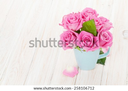 Fresh spring garden pink roses bouquet on white wooden table with copy space - stock photo